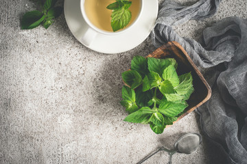 Fresh organic mint and tea on a gray background