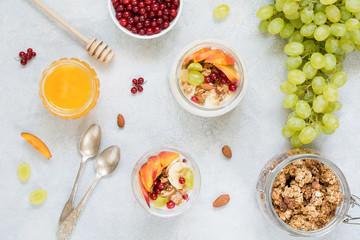 Healthy breakfast food table: granola, fruits, yogurt and honey. Table top view