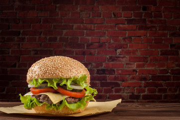 Delicious cheeseburger with salad ingredients on a grilled beef patty on a rustic wooden table with copyspace