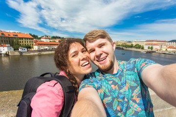 Handsome couple taking selfie with mobile smart phone camera in european city. Vacation, love, travel and holiday concept.