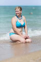 Overweight blonde in bikini sitting in waters edge