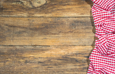 Rustic tablecloth red white checked on wooden table background with copy space