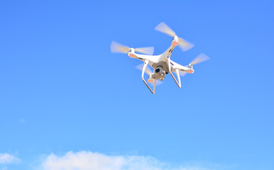 Drone camera flying for take a picture on blue sky background