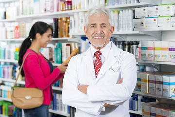Smiling Chemist Standing Arms Crossed While Customer Choosing Pr