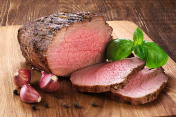 Baked meat, garlic and basil on a wooden background. Roast beef.