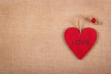 Red wooden heart pendant on a natural linen background. A wooden valentine on a natural background. Backgrounds and textures. Copy space