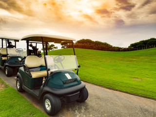 Golf carts or golf club cars on foot path in a green golf course fairway with beautiful sunset or sunrise sky in a sunny day