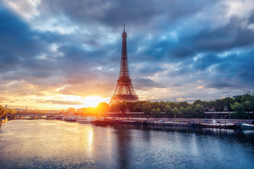The Eiffel Tower at sunrise. Paris, France. Beautiful skyline of with rising sun and dramatic clouds.