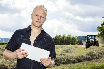 Man with tablet PC in haymaking