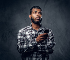 Black bearded male dressed in a fleece shirt using a smartphone.