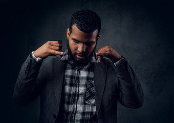 Black hipster male dressed in a fleece shirt and a jacket.