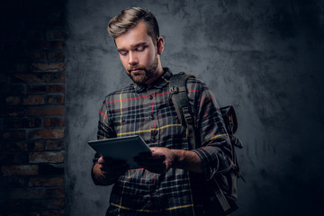 A man holds tablet PC over grey background.