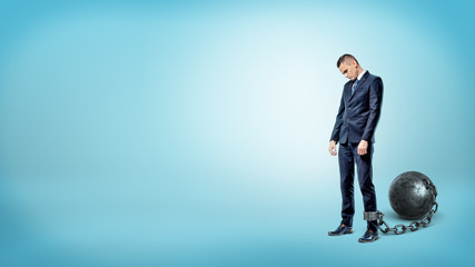 A depressed businessman on blue background stands with a lowered head while chained to an iron ball.