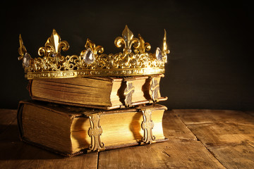 low key of beautiful queen/king crown on old books. vintage filtered. fantasy medieval period Fototapete
