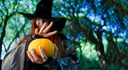 Photo of witch with pumpkin reading spells
