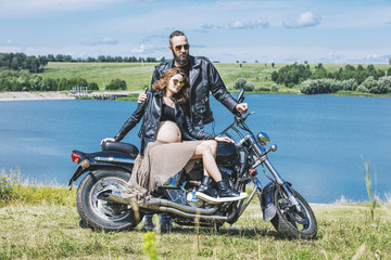 Beautiful couple man and woman on a motorcycle on a background of water and sky happy