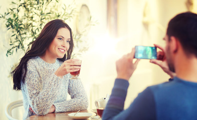 man taking picture of woman by smartphone at cafe