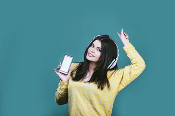 Model woman young and beautiful in the style of pop art on a blue background with a picture of headphones with a mobile phone