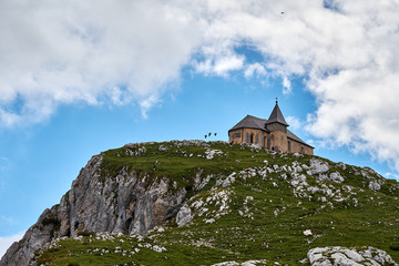 Flock of crows flying around the ancient german chapel Maria am Stein on the very top of Dobratch summit near Villach in Austria