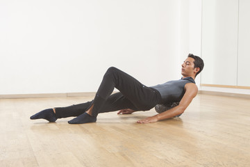 professional ballet dancer stretching and warming up using foam roller
