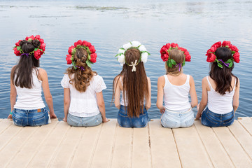 Back view of five young ladies, wearing flower wreaths, jeans and white tshirts. Group of friends sitting on the side of the pool or on pier. Pool party, summer vacation. Banner for website.
