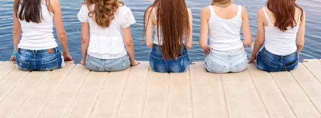 Back view of five young ladies, wearing jeans and white tshirts. Group of friends sitting on the side of the pool or on pier. Pool party, summer vacation. Banner for website.