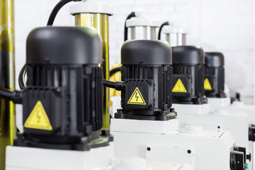 Linear row of black electric motors.
