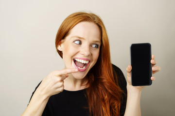 glückliche frau zeigt mit dem finger auf ihr mobiltelefon