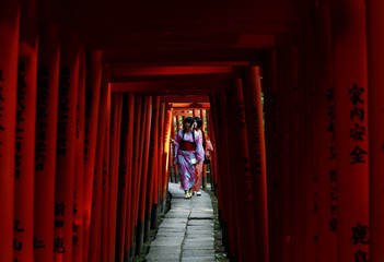 Women dressed in yukata, or a casual summer kimonos, walk through red-coloured wooden torii gates at the Nezu shrine in Tokyo