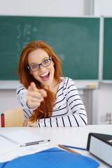lachende frau in der schule zeigt mit dem finger nach vorne