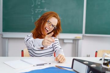 lachende studentin zeigt mit dem finger nach vorn