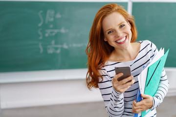 lachende lehrerin mit handy in der schule