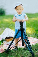 Serious boy works with a tripod