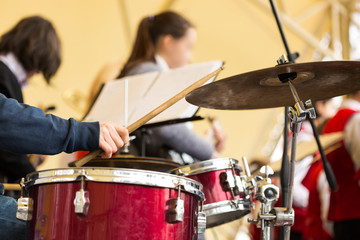 Poster Caraïben jazz band music performance concept - orchestra drum kit during the concert, closeup on hand of musician playing on percussion instruments and ride cymbal, selective focus