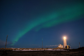 Northern lights or Aurora Borealis over the lighthouse near Reykjavik, Iceland