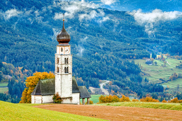 Wall Mural - View of idyllic mountain scenery in the Dolomites with St. Valentin Church in beautiful morning light at sunrise, village of Seis am Schlern on background, South Tyrol, Italy.
