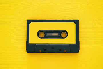 Retro cassette tape over yellow wooden table. top view.