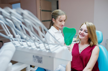 Beautiful dentist showing her patient's new teeth through the mirror in dental cabinet.