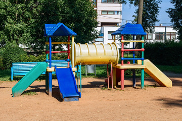 Colorful chilgren playground. Public park near houses  with grass and trees.