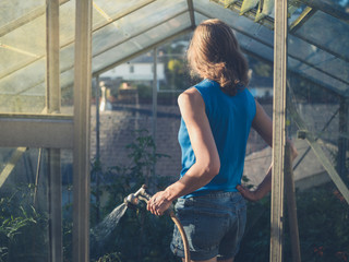 Young woman watering tomatoes in her greenhouse