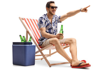 Tourist with a beer sitting in a deck chair and pointing