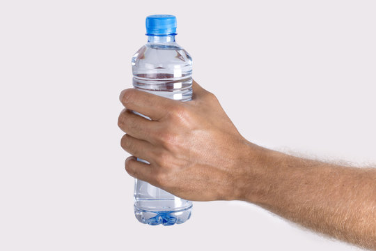 Close up man's hand Holding Bottle of  Water isolated on white background