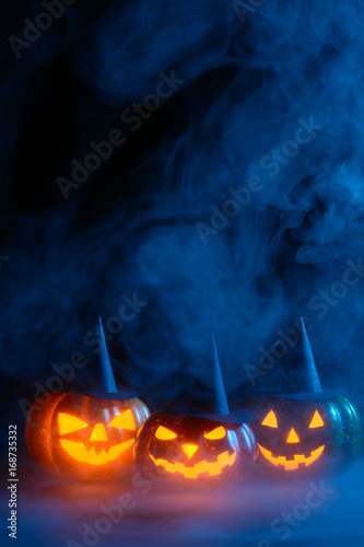Glowing pumpkins in blue smoke