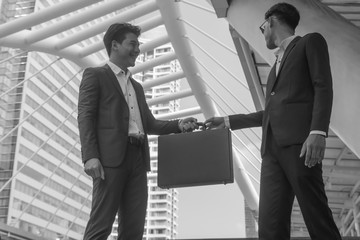 Asian business people transfer briefcase in monochrome.