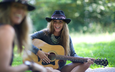woman playing guitar at park. music, smiling, young, hat.