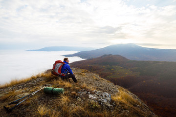 Young tourist hiker with backpack siting and relaxing on the top of the mountain and looking at beautiful yellow autumn landscape sunset over clouds