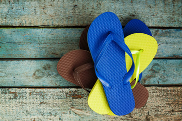 stack of several pairs of multi-colored rubber flip flops on a blue wooden background