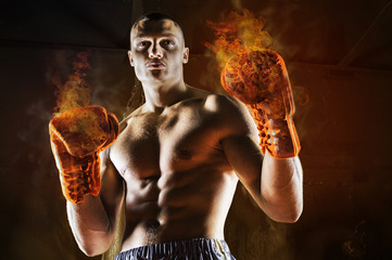 Conceptual Portrait of brutal boxer in fire sparks and smoke.