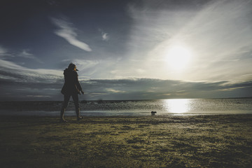 Young woman walking with her dog on the beach