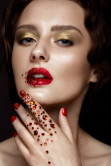 Beautiful girl with evening make-up, red lips in rhinestones and design manicure nails. beauty face. Photos shot in studio